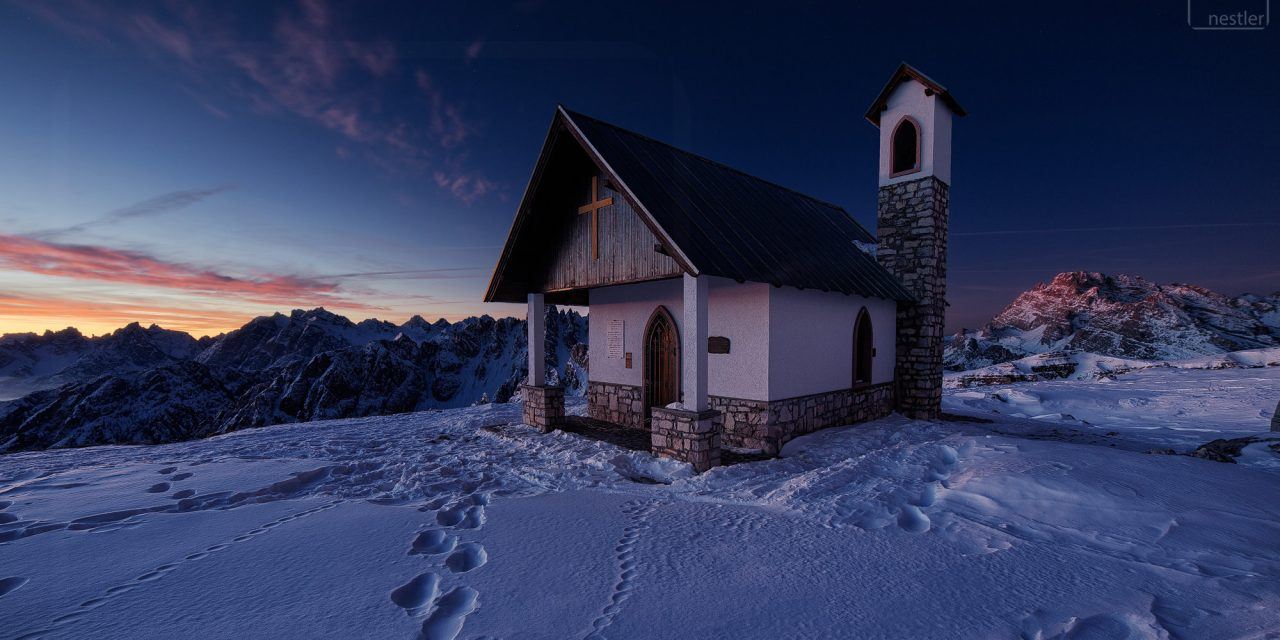 A chapel in the mountains at sunrise in the Italian Dolomites in Winter
